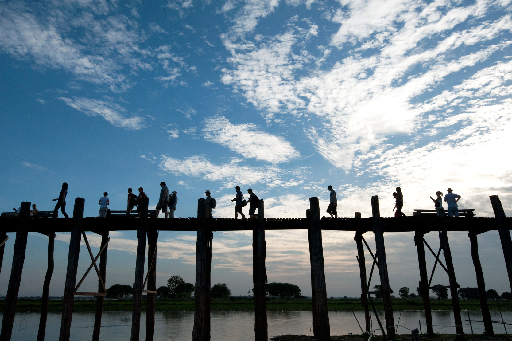 Dramatic sky silhouetting people crossing U Bein's Bridge, supported by 984 teak posts over 1.2 km distance across Thaumthaman Lake, Mandalay.