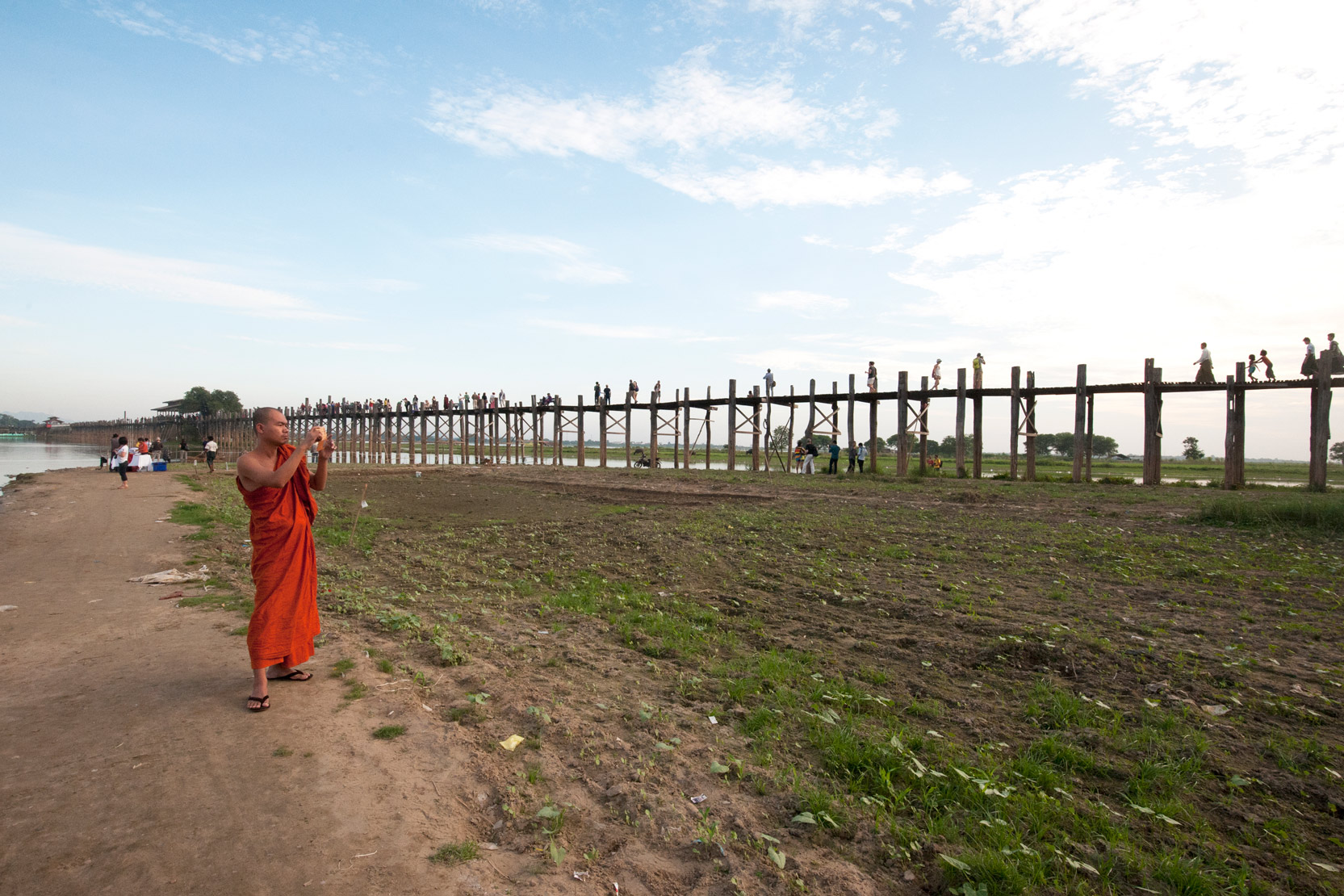 Orange robed monk photographing people crossing U Bein's Bridge, supported by 984 teak posts over Thaumthaman Lake, Mandalay.