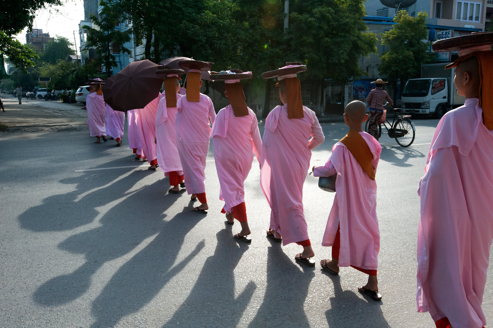 Line of Buddhist nuns dressed in pink robes, heads covered, alms bowls on their heads, crossing main road in Mandalay.