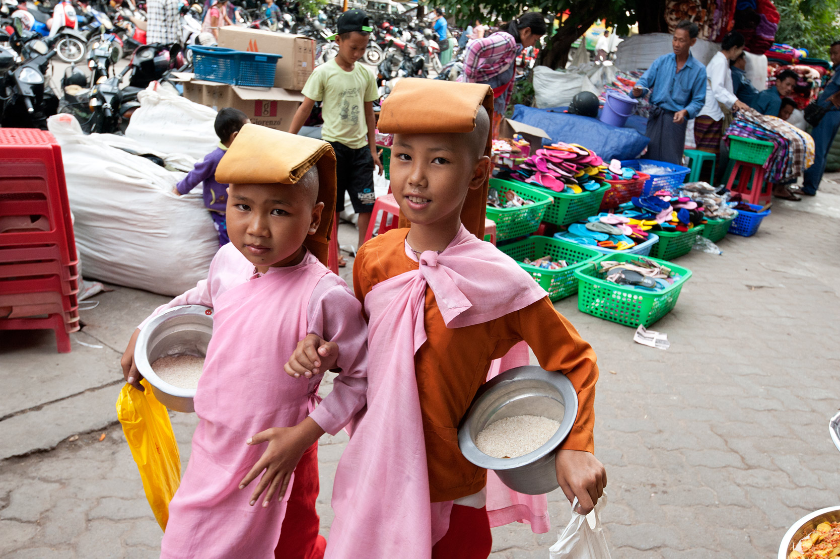 Two young shaven headed Buddhist nuns in pink robes, heads covered, alms bowls full of donated rice in Mandalay street market, Myanmar.