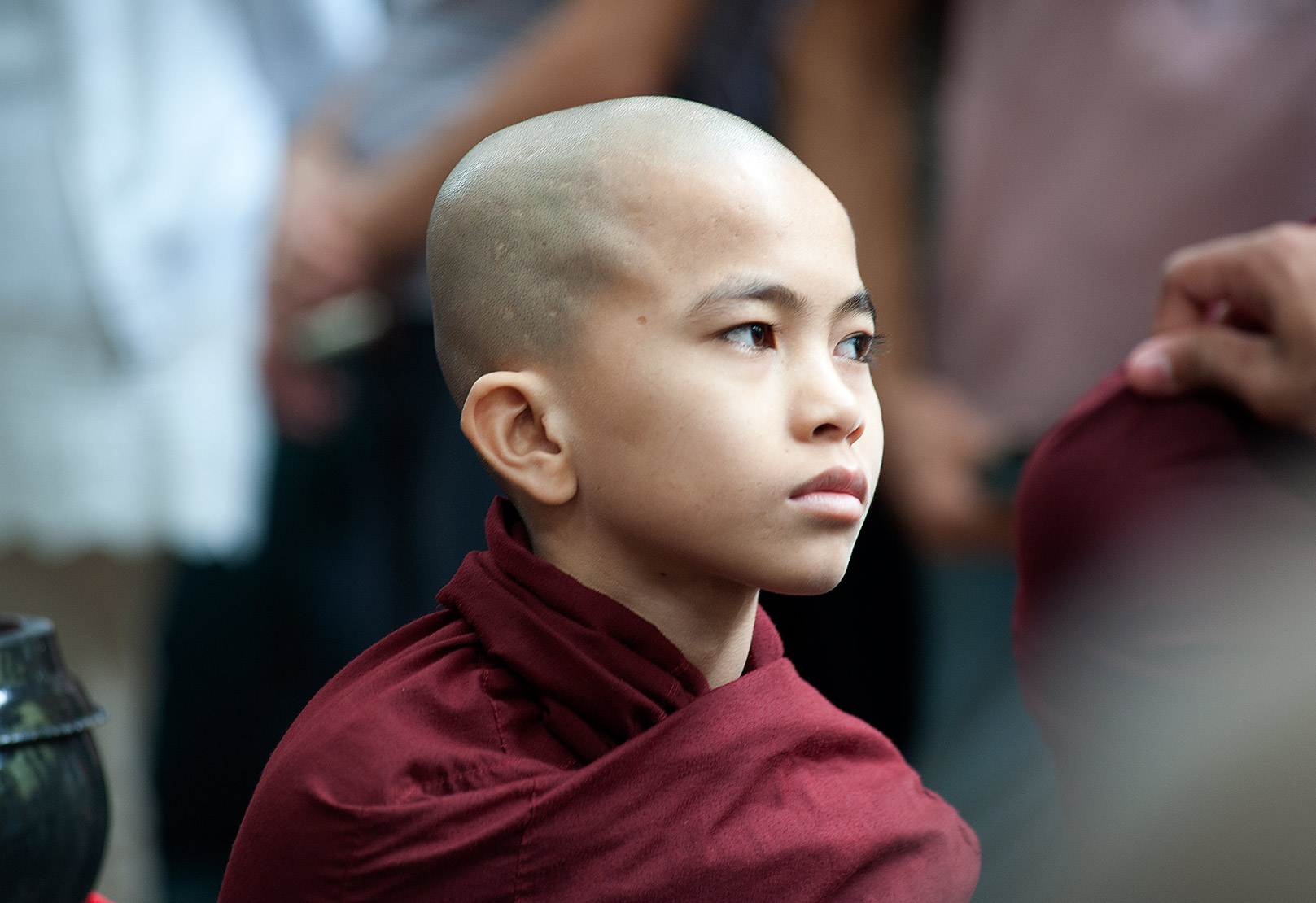 Thoughtful, shaven headed Buddhist monk in red robes waiting in line for lunch at the Maha Gandayon monastery, Mandalay.
