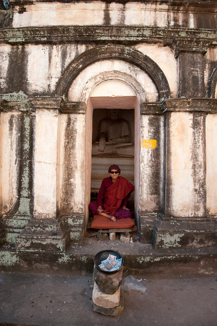Red robed Buddhist monk sitting in front of Buddha statue in stone carved temple, collecting alms, Shwe Ba Hill village, Monywa.