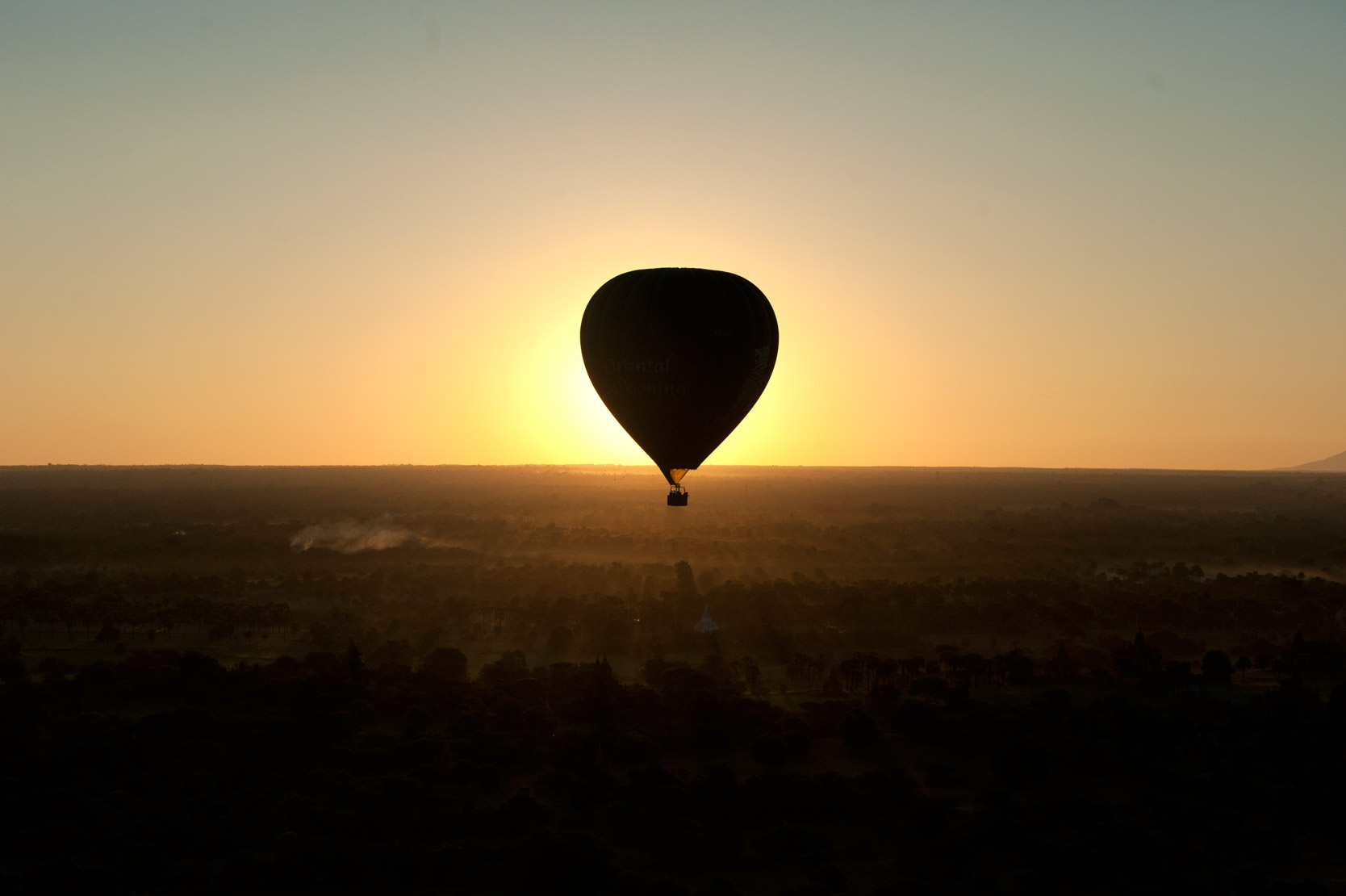 Hot air balloon backlit at sunrise, flying over the temples of Bagan, Mandalay Division.
