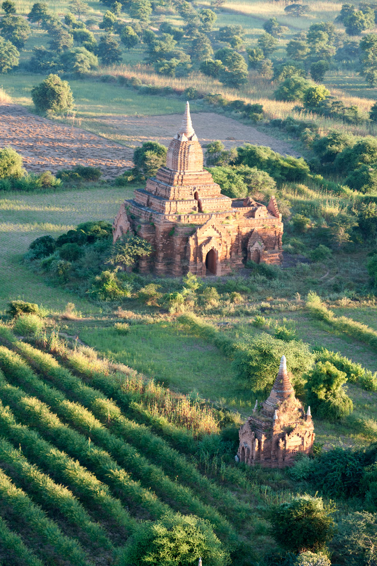Small Buddhist temple lit by morning sunlight amongst fertile green farmland in Bagan, seen from the air, Mandalay Division.