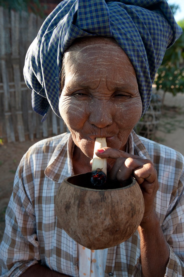 Village woman smoking large, home rolled cigarette, made from village grown tobacco, Old Bagan, Mandalay Division.