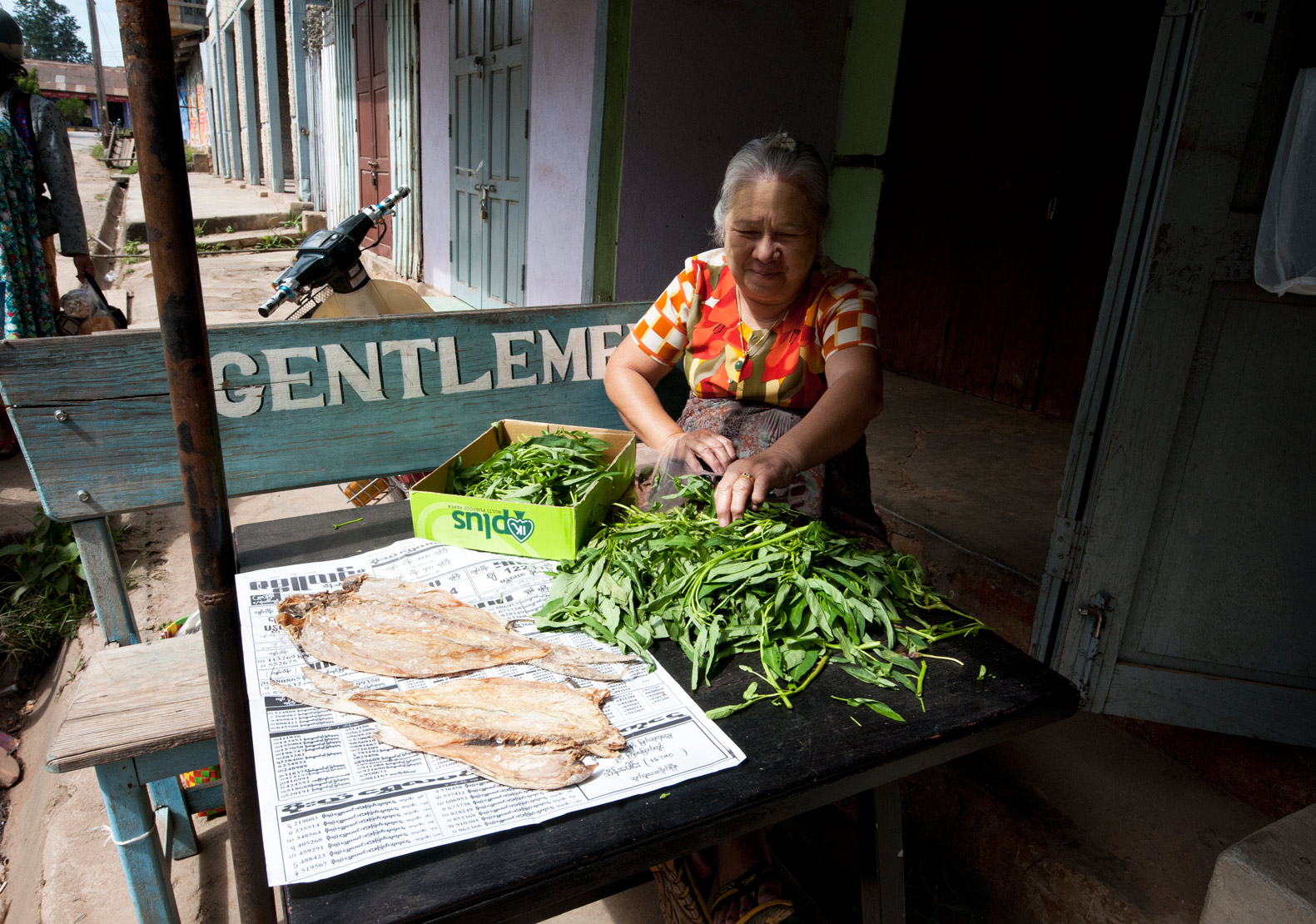Woman sitting outside her house, preparing green vegetables, fish drying on the table, Kalaw, Shan state, Myanmar.