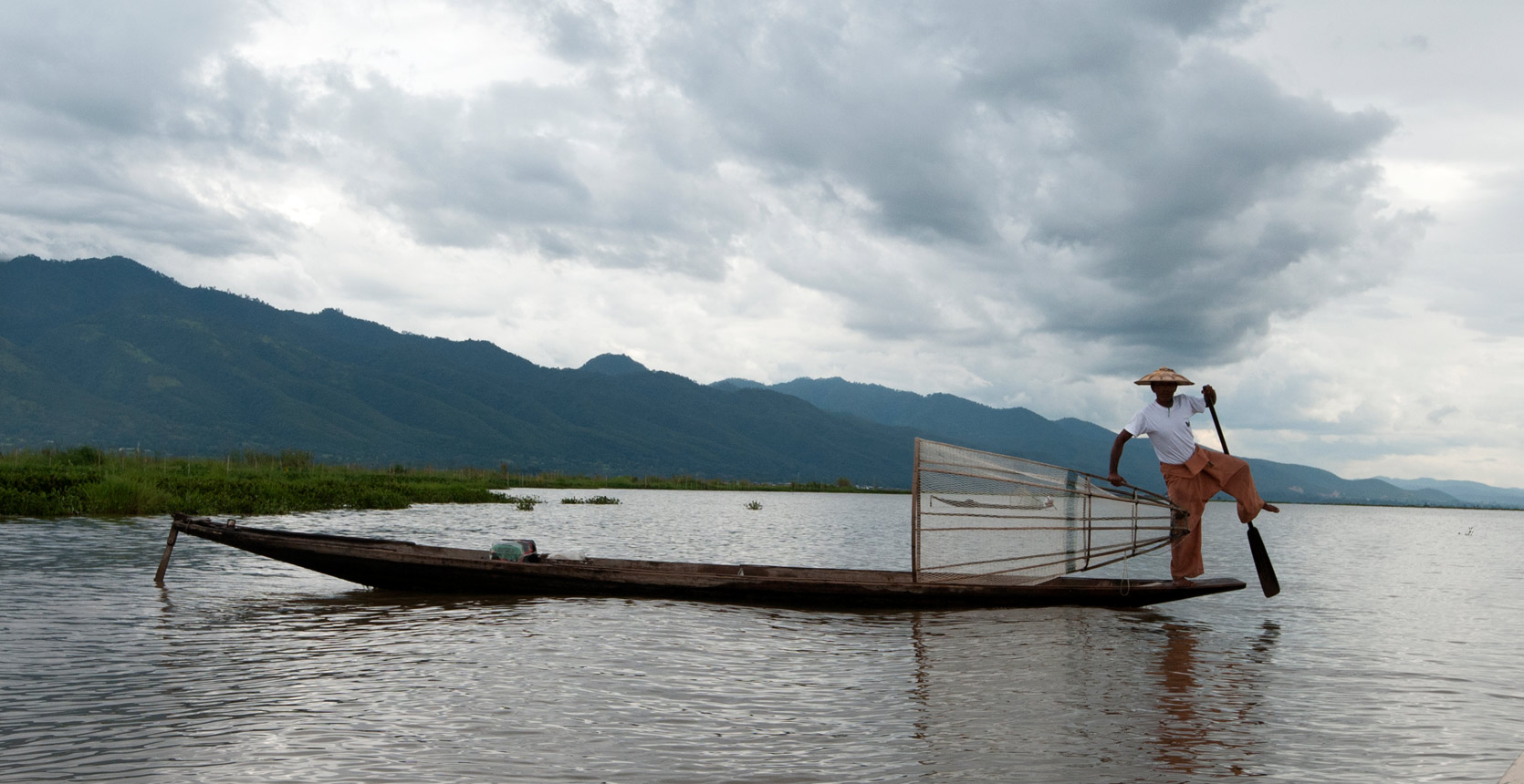 Leg rowing fisherman from the Intha people, standing on boat with cylindrical net and demonstrating leg rowing position, Inle lake, Shan state.
