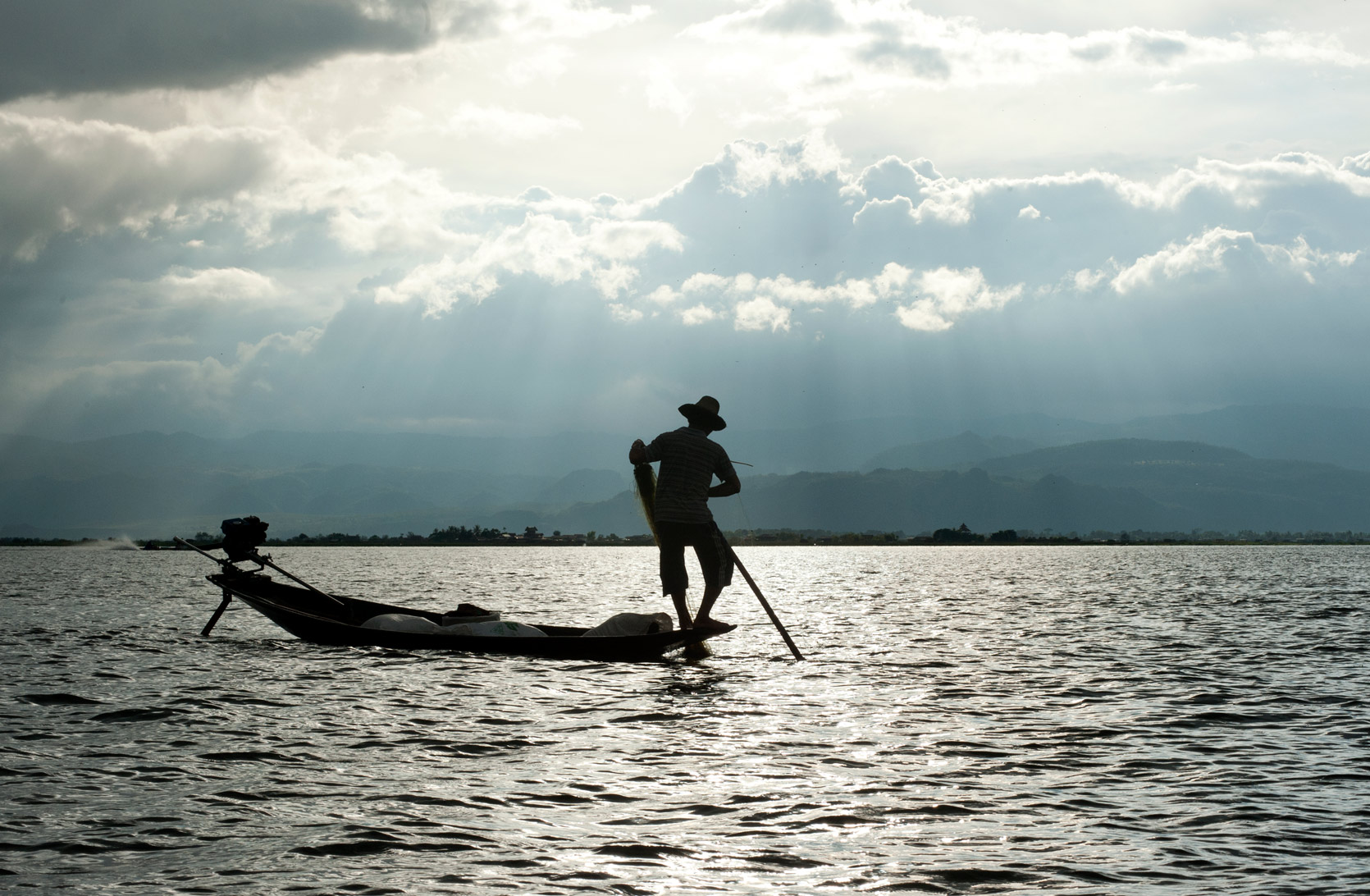 Silhouette of leg rowing fisherman from the Intha people, standing on boat untangling his net, Inle lake, Shan state.