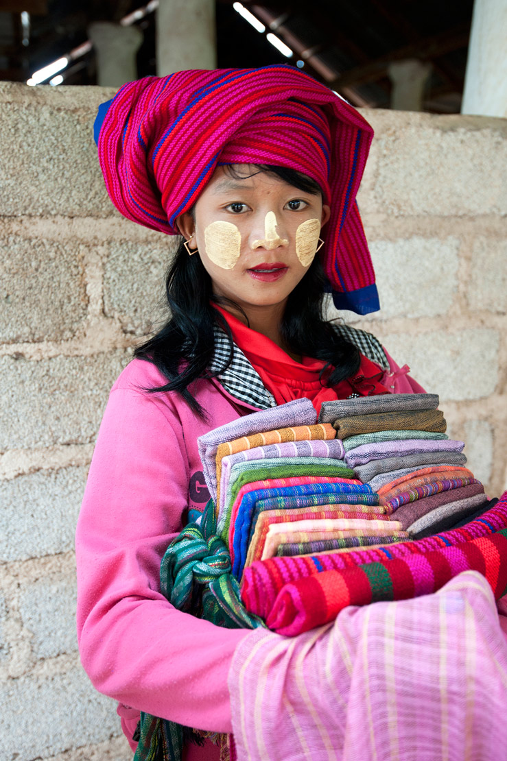 Young girl with thanaka paste on her cheeks and nose, selling colourful scarves and sarongs at Nyaung Oak Monastery, Indein, Inle Lake, Shan state.
