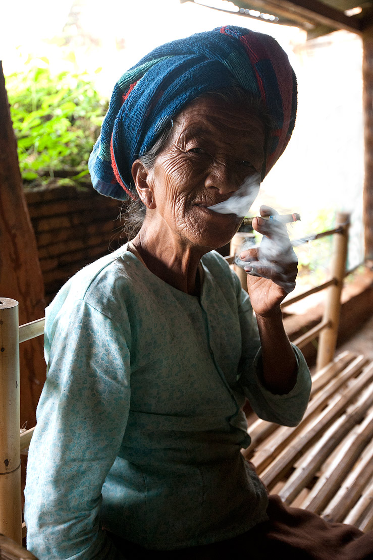Woman with blue headcloth and wrinkled face smoking locally made cigar at Nyaung Oak monastery, Indein, Inle Lake, Shan state.