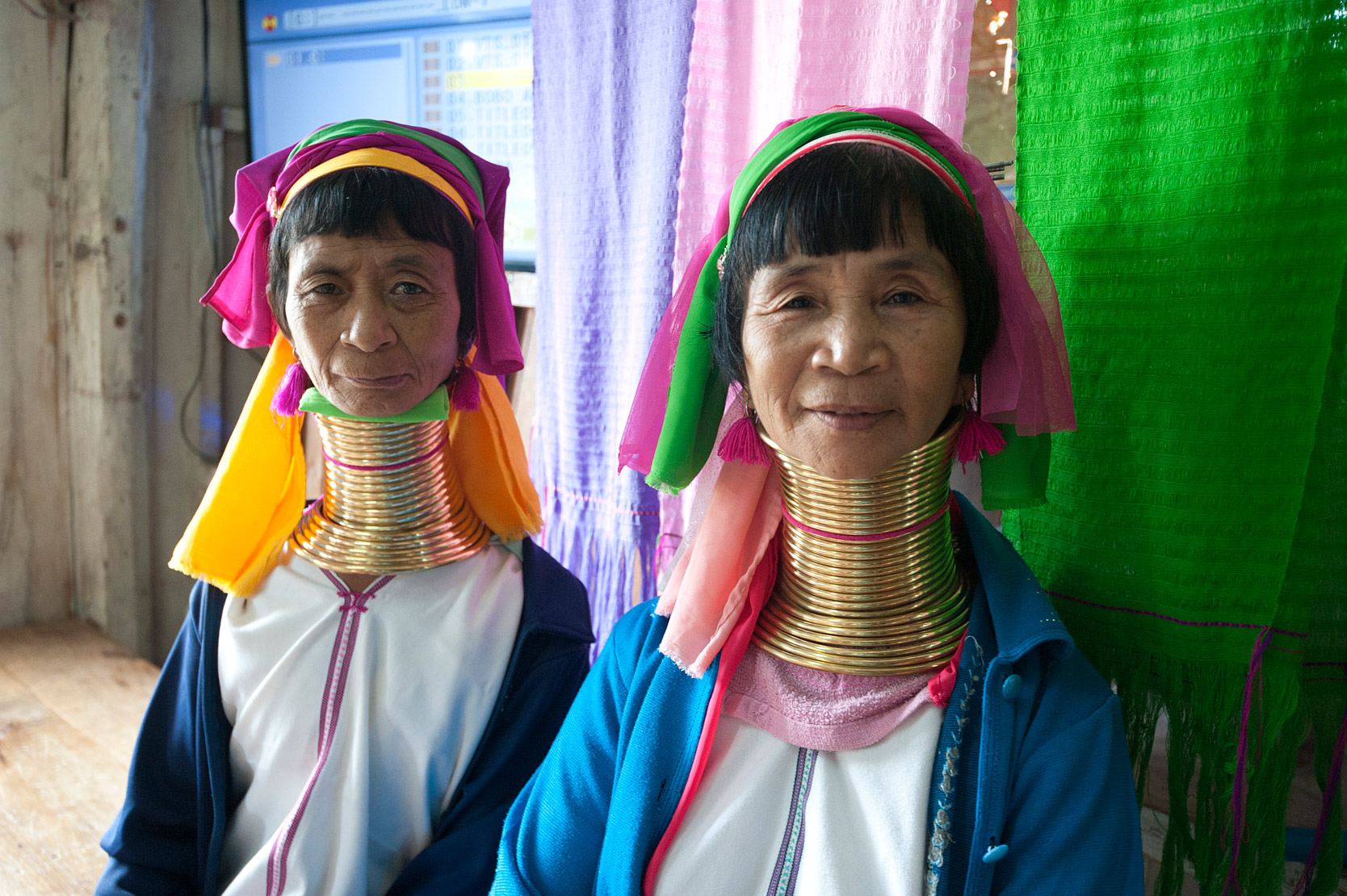 Paduang women, sisters from Ywama village, wearing traditional head cloths, brass neck rings, knee rings and metal bracelets, Inle Lake, Shan state.