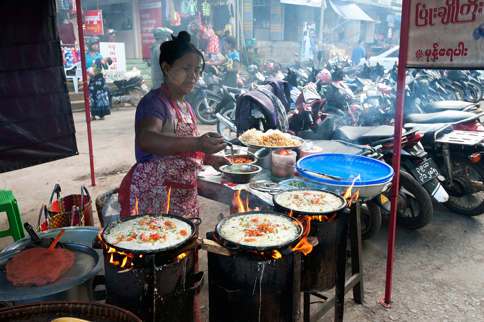 Woman frying rice pancakes with fillings on a street market fast food stall in Pyin Oo Lwyn, Mandalay Division, Myanmar.