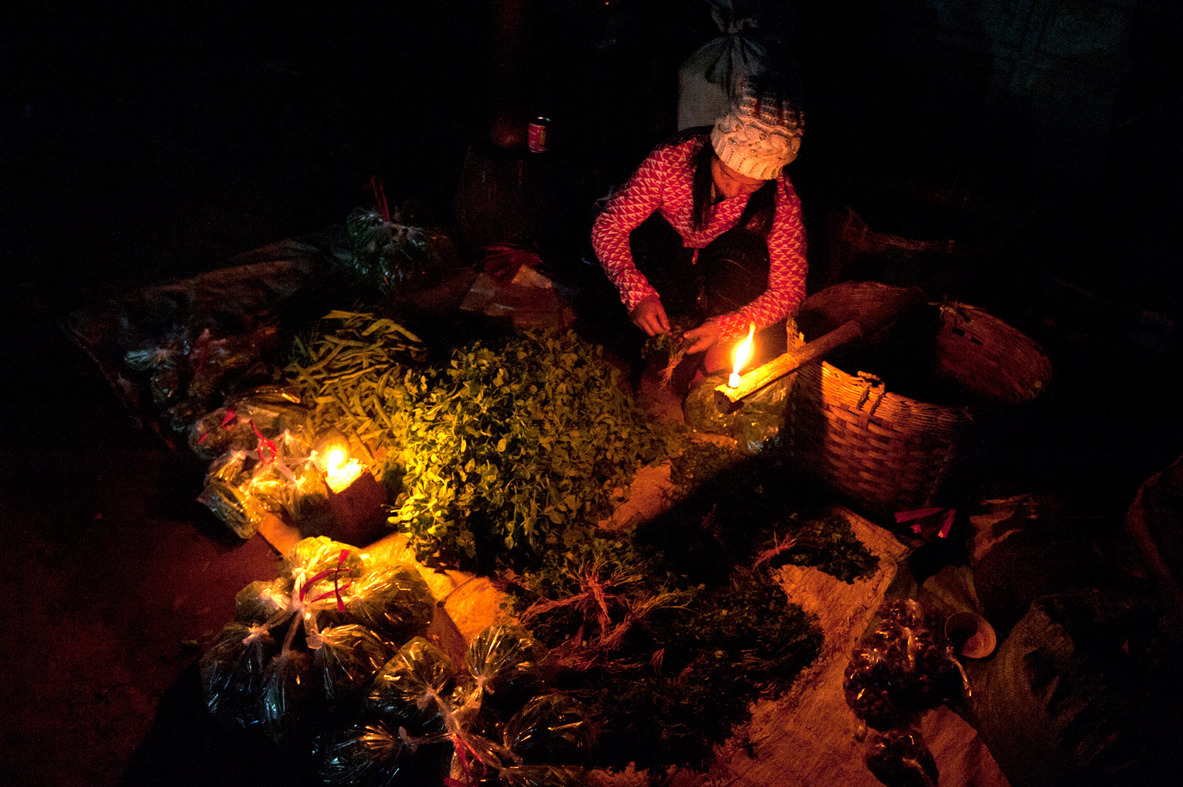 Woman preparing and selling fresh vegetables and herbs in 'candlelight street market' in Hsipaw, Shan state, Myanmar.