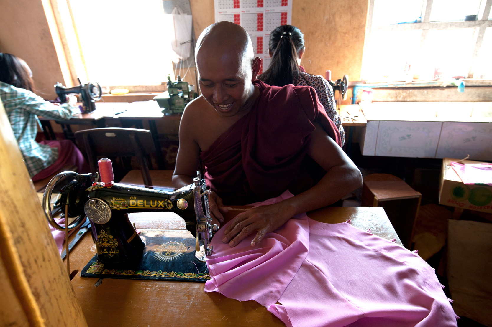 Monk sewing nun's pink robes in Ma Ni Zaw Tar Yar Ma Monastery