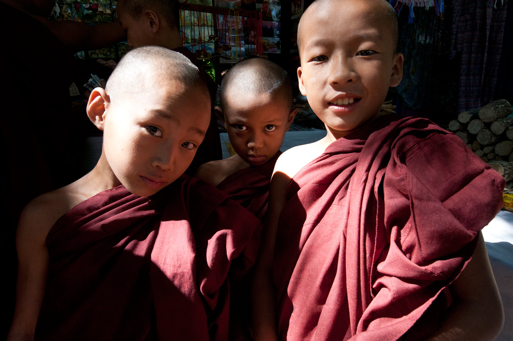 Three young shaven headed monks in red robes on a day off visiting Mingun looking at a market stall, Mingun.