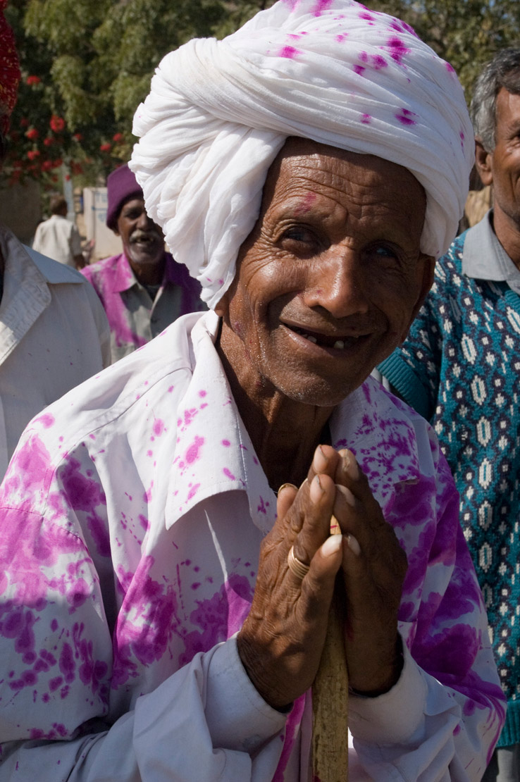 Friendly man offering 'Namaste' greeting, splashed with pink colourafter ceremony, Chattorgarh